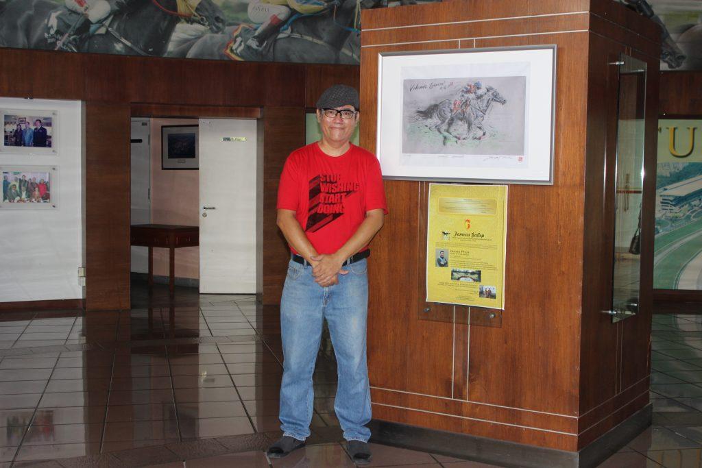 潘瑞全站在他的作品旁。地点在雪兰莪赛马公会大厅。